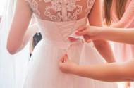 49464080 - helping the bride to put her wedding dress on